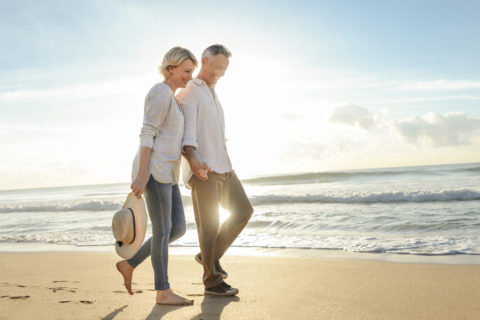 Mature couple walking on the beach at sunrise