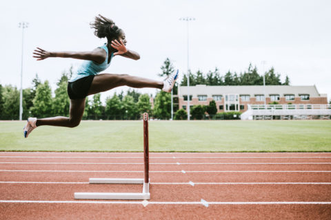 Woman Athlete Runs Hurdles for Track and Field